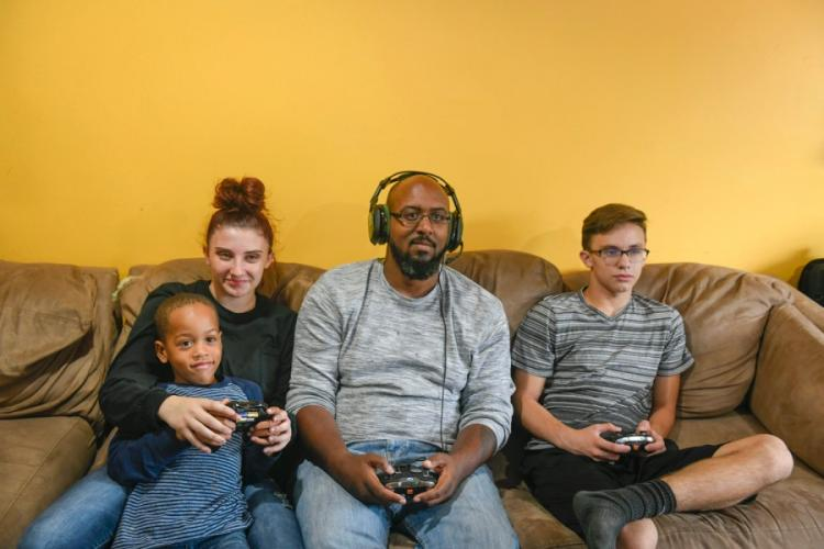 James Martin, center, a Marine veteran of Iraq and Afghanistan, plays video games Sept. 23, 2018, with his family in his home just outside of Pittsburgh, Pa. Martin, a volunteer for the Wounded Warrior Project, hopes to connect veterans during the coronavirus pandemic through online gaming. WOUNDED WARRIOR PROJECT