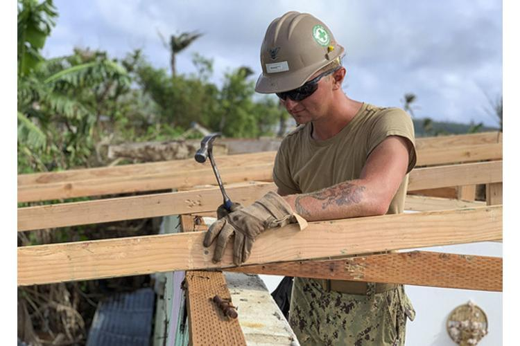 TINIAN, Northern Mariana Islands --- Builder 3rd Class Matthew Winnett, assigned to Naval Mobile Construction Battalion 3, Det. Tinian, nails in a truss, Jan. 25, for a temporary emergency roof for a home that was damaged during Super Typhoon Yutu. (Photo by Navy/CECN Manual Torres)