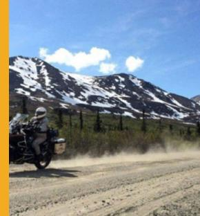Chris Day churns up dust on the Denali Highway of Alaska. Eight friends decided to take an 865-mile ride around Alaska. (Charles Fleming/Los Angeles Times)