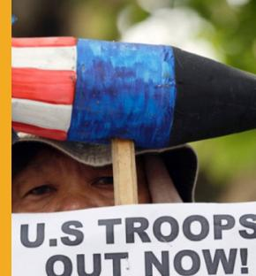 A protester holds a sign demanding U.S. troops to leave the Philippines during a rally at the US Embassy in Manila on Thursday, Oct. 16, 2014. Police Chief Inspector Gil Domingo said Marine Pfc. Joseph Scott Pemberton was the last person seen with the victim late Saturday, when they checked into a motel after meeting in a bar in Olongapo city northwest of Manila. (Bullit Marquez/AP)