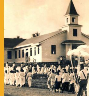 In this historic photo, several villagers, clad in white, walk in a religious procession in Barrigada during a patron saint's feast day. The village celebrates three fiestas throughout the year for San Vicente, San Roke, and San Ramon. Photo by Capuchin