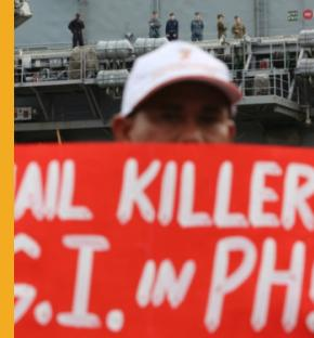 A Filipino activist hold a slogan during a rally near the USS Peleliu at the Subic Bay free port, about 80 kilometers (50 miles) northwest of Manila on Saturday Oct. 18, 2014. The group placed a subpoena on barb wires for accused U.S. Marine Pfc. Joseph Scott Pemberton who is said to be detained at the USS Peleliu after being allegedly killing transgender Jennifer Laude inside a motel in Olongapo.  Aaron Favila/AP