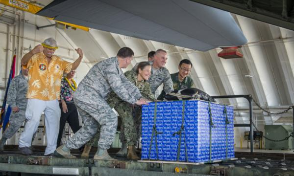 Military and civilian leaders push a box onto a C-130J Super Hercules during the 2017 Operation Christmas Drop Push Ceremony Dec. 11, 2017, at Andersen Air Force Base, Guam. This year marks 66 years of Operation Christmas Drop which provides joint airlift training opportunities for both peace and wartime efforts.(U.S. Air Force Photo by Airman 1st Class Christopher Quail)
