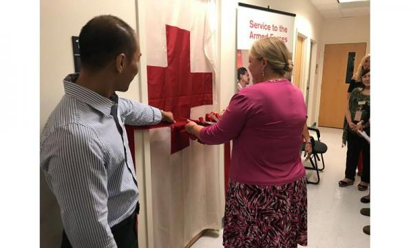 Mrs. Lynae Cox, wife of Brig. Gen. Douglas Cox, 36th Wing commander, cuts a ribbon during the official opening of the new Red Cross service office Dec. 6, 2017, at Andersen Air Force Base, Guam. The office marks the first time in 20 years that the Red Cross provided on-base services to service members. (U.S. Air Force photo by Airman 1st Class Christopher Quail)