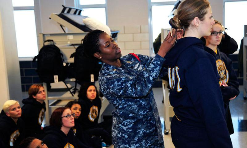 GREAT LAKES, Ill. (Jan. 6, 2015) Chief Logistics Specialist Natali Philip, left, a recruit division commander, uses a ruler to measure the hair of Seaman Recruit Briana Cochems, from Los Angeles, to show proper hair grooming standards to new recruits at Recruit Training Command. (U.S. Navy Photo by Lt. Adam Demeter/Released)