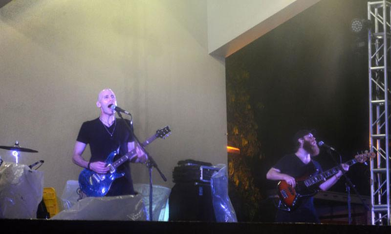 Alternative rock band Vertical Horizon's Matthew Scannell, left, lead singer and guitarist and Jeffrey Jarvis, right, bass guitarist, perform for Team Andersen audience members Jan. 6, 2015, at the Arc Light Amphitheater at Andersen Air Force Base, Guam. The band played through rain storms and wind to provide entertainment for Andersen members and their families as part of a Armed Forces Entertainment tour that brings the band to several bases across the Pacific.