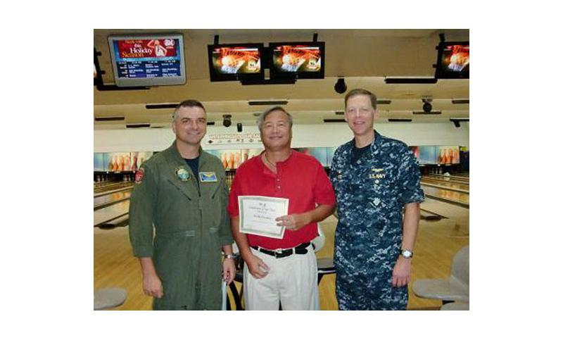MWRStar Employee: U.S. Naval Base Guam Commanding Officer Capt. Mike Ward, right, and NBG Executive Officer Cmdr. Christopher Flis, left, present Orote Point Lanes Manager Kelly Lizama with Morale, Welfare and Recreation (MWR) Guam's Employee of the Year award during a ceremony at the bowling alley on NBG Jan. 4. Photo courtesy of MWR Guam