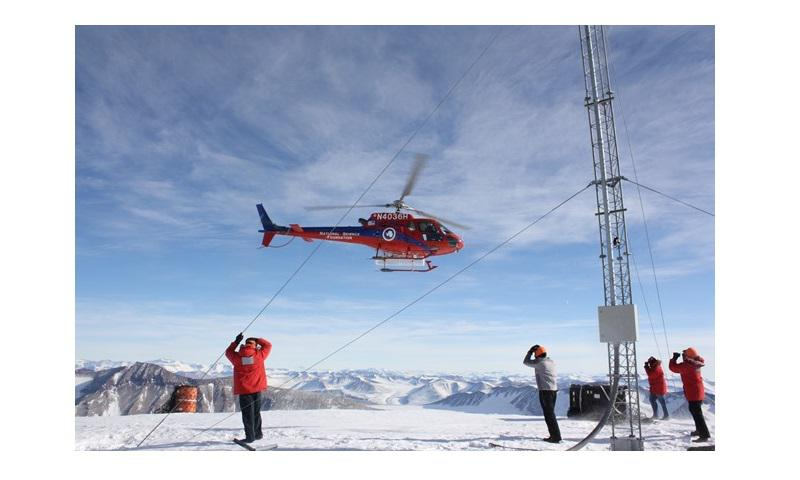 Battling high winds and frigid temperatures, seismic maintainers from the Air Force Technical Applications Center based at Patrick Air Force Base, Fla., receive fuel resupply via helicopter from the National Science Foundation at AFTAC's repeater site at Mount Newell, Antarctica, Nov. 1, 2017. (Air Force photo by Brian Fox)