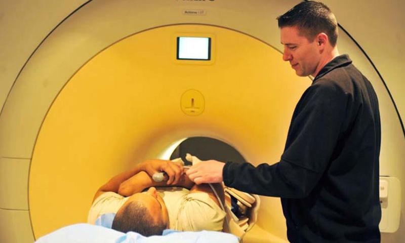 Cody Turner, an MRI technician with the 455th Medical Support Squadron, prepares a patient for his magnetic resonance imaging scan at Bagram Air Field, Afghanistan, on April 3, 2012. (U.S. Air Force)