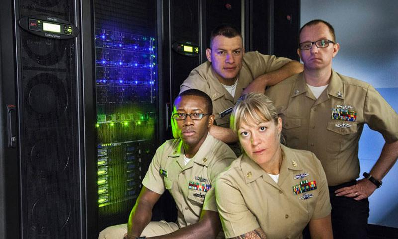 The first cohort of enlisted servicemembers to attend the Naval Postgraduate School's master of applied cyber operations degree program, clockwise from left: Information Systems Technician Chief Deyan Dontchev, IT1 Thomas Skoff, ITC Javon Burden and ITC Rachel Doucet pose at NPS' Hamming High Performance Computing Lab in 2013. (U.S. Navy)