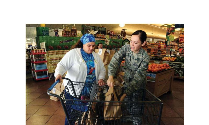 Senior Airman Rachel Hutson places a grocery bag in a commissary shopper's cart at Little Rock Air Force Base, Ark., on Feb. 5, 2013. (Kaylee Clark/Courtesy of the U.S. Air Force)