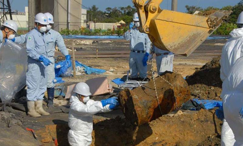 Japan Ministry of Defense workers remove a drum Jan. 28, 2014, from a soccer field next to Amelia Earhart Intermediate School on Kadena Air Base where 22 dioxin- and herbicide-laced drums were unearthed last summer. (Travis J. Tritten/Stars and Stripes)