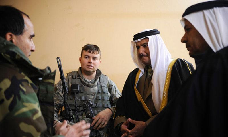 In a 2008 file photo, an interpreter, left, translates for U.S. Army Capt. Matthew Schlosser, 1st Battalion, 8th Infantry Regiment, Fort Carson, Colo., during a meeting with sheiks at an Iraqi police station in Nimrud, Iraq. (DOD)