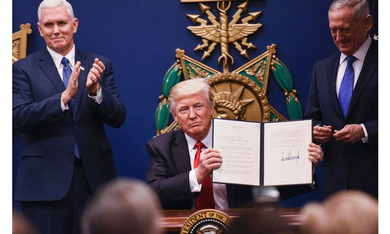 Vice President Mike Pence and Defense Secretary Jim Mattis look on as President Donald Trump holds up an executive order to increase military readiness that he signed Friday at the Pentagon. (COREY DICKSTEIN/STARS AND STRIPES)