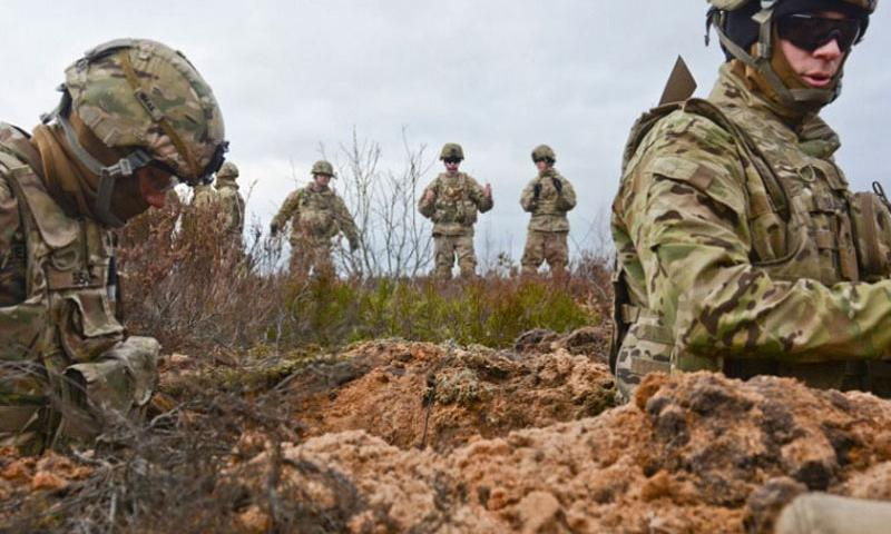 Soldiers of 3rd Squadron, 2nd Cavalry Regiment, stationed at Vilseck, Germany, stand in the trench and place dirt around the 43-pound charge craters to keep them stable so they can be buried in an upright position during a demolition training exercise at Adazi Training Area in Latvia, Jan. 30, 2016. (Steven Colvin/U.S. Army photo)