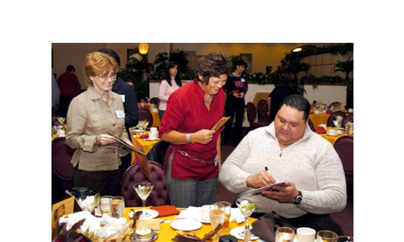 Chad Rowan, better known as Akebono, signs autographs for members of the Yokota Officers Spouses Club after speaking at the Yokota Officers club Nov. 6, 2007. Rowan, a legendary sumo wrestler, lives around Yokota. (Christopher B. Stoltz / Stars and Stripes)