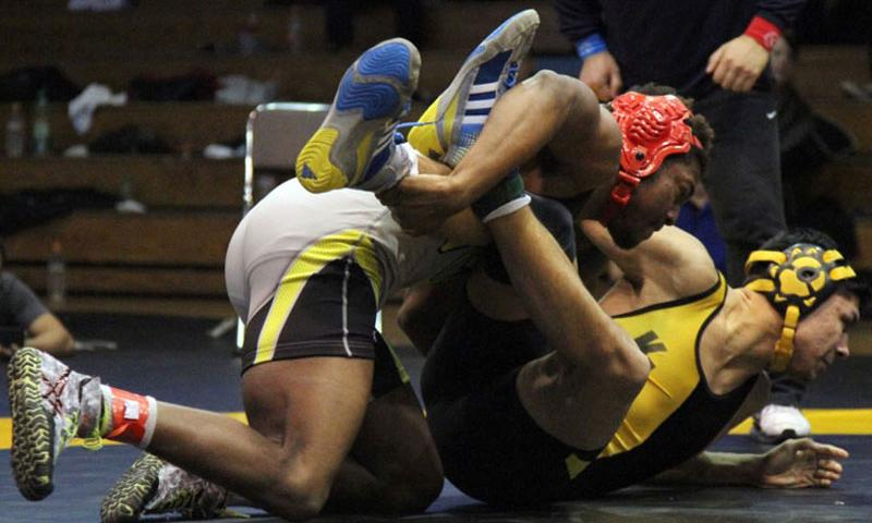 Nile C. Kinnick's Dre Paylor gets the edge on Kadena's Ricky Salinas during Friday's 168-pound Far East tournament title bout. Paylor won by technical fall 15-4. (Haeley Deeney/Special to Stars and Stripes)