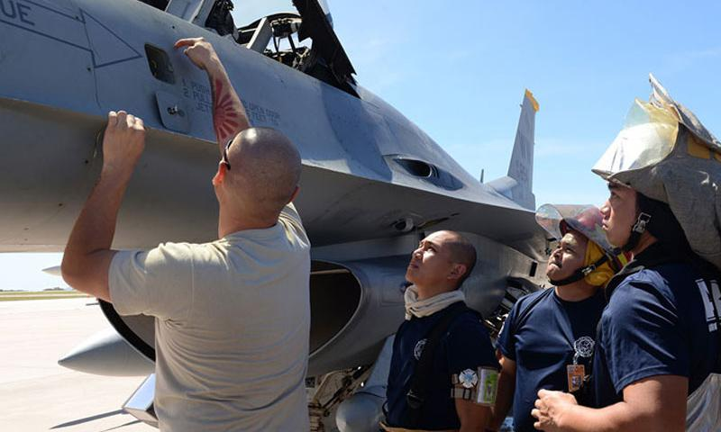 An F-16 maintainer deployed from the 35th Fighter Wing out of Misawa Air Base, Japan, shows Saipan firefighters various hazardous points on a F-16 Fighting Falcon during training Feb. 12, 2015, at the Saipan International Airport, Saipan in the Commonwealth of Northern Marianas Islands approximately 130 miles north of Guam. The training was geared towards preparing Saipan first responders for a runway emergency involving the F-16. (U.S. Air Force photo by Senior Airman Cierra Presentado/Released)