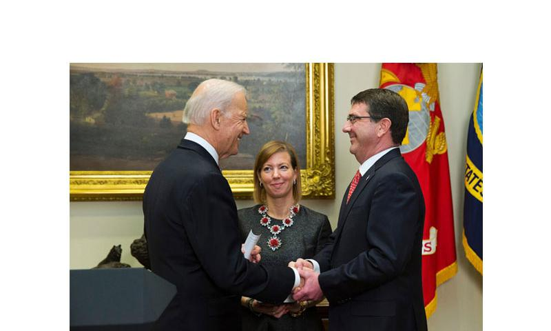 Stephanie Carter watches at center as her husband Ash Carter, right, shakes hands with Vice President Joe Biden after being sworn in as the new Defense Secretary, Tuesday, Feb. 17, 2015, in the Roosevelt Room of the White House in Washington. (Evan Vucci/AP)