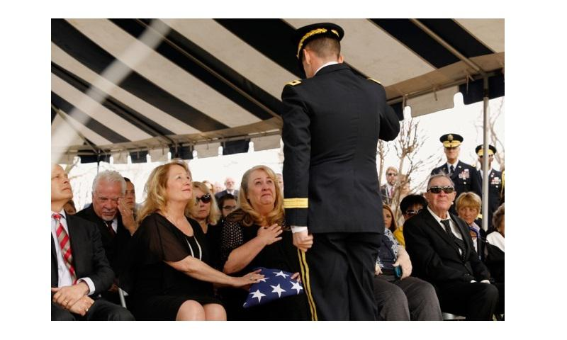 Sisters Cecile Moore Rainey, left, and Julie Moore Orlowski, right, receive the flag of their father, retired Lt. Gen. Hal Moore at his burial services Friday, Feb. 17, 2017, at Fort Benning, Georgia. (TODD J. VAN EMST/OPELIKA-AUBURN NEWS VIA AP)