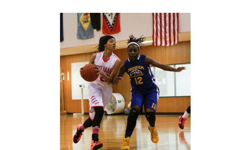 Zama's Ti'Ara Carroll looks for room to maneuver around Yokota's Jamia Bailey during Wednesday's 2015 Division II girls Far East championship game. Yokota beat Zama 53-40. (Kayla Bodwin/Special to Stars and Stripes)