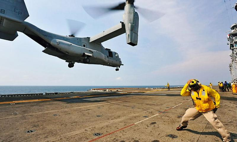 A crewman braces as a MV-22 Osprey takes off from a Navy vessel in the Gulf of Thailand on Feb. 19, 2013, during the Cobra Gold exercise. (MICHAEL ACHTERLING/U.S. NAVY, FLICKR)