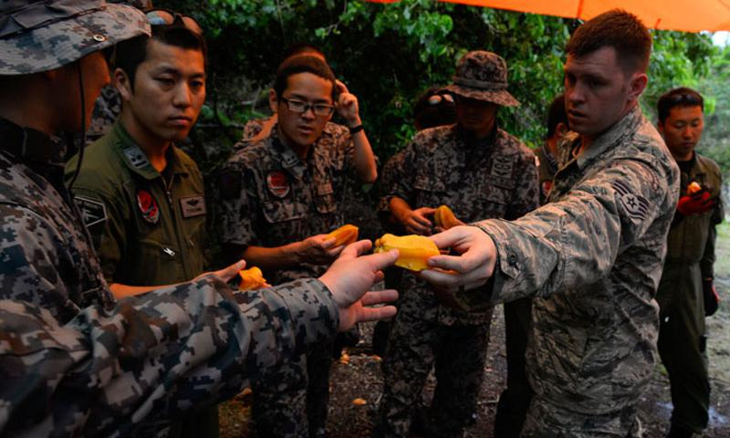 Staff Sgt. Levi Wood, survival, evasion, resistance and escape instructor assigned to the 353rd Combat Training Squadron, shares star fruit with Japan Air Self-Defense Force airmen during a jungle survival workshop Feb. 16, 2016, at Andersen Air Force Base, Guam. (U.S. Air Force photo by Staff Sgt. Alexander W. Riedel/Released)