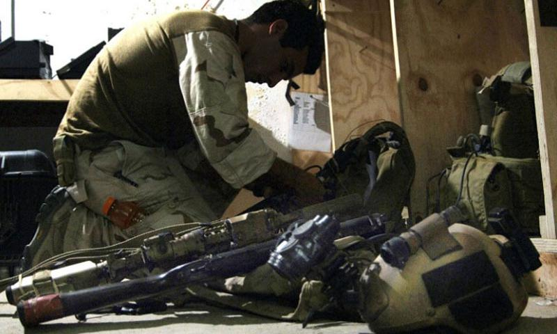 In a 2007 file photo, a U.S. Special Operations Forces member prepares his gear for an evening mission in western Iraq. (Eli J. Medellin/U.S. Navy)