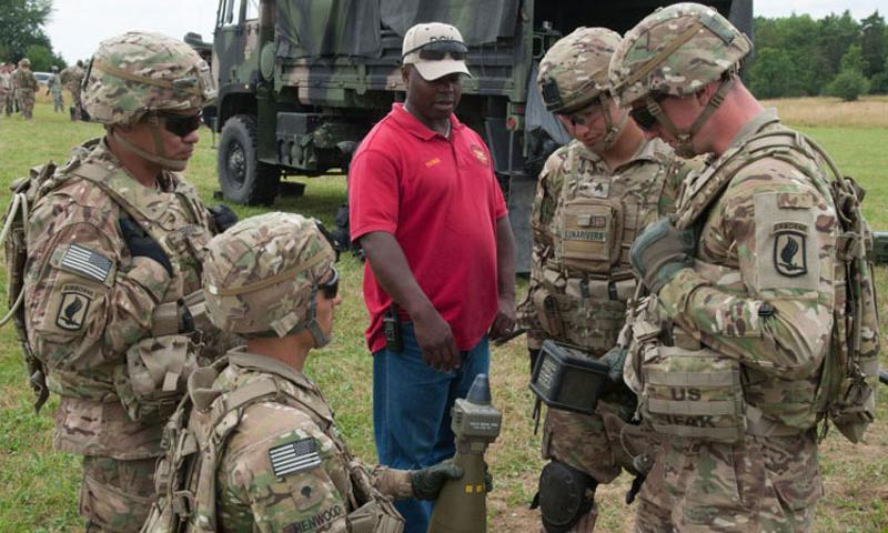 Patrick Stewart, a civilian training instructor with Subsystems Technology, works hand in hand with artillerymen from the 173rd Airborne Brigade Combat Team at Vilseck, Germany, July 23, 2015. U.S. Army Europe's inspector general's office is conducting a survey of USAREUR's civilian workforce to see if current policies regarding overseas employment are being fairly applied. (Michael S. Darnell/Stars and Stripes)