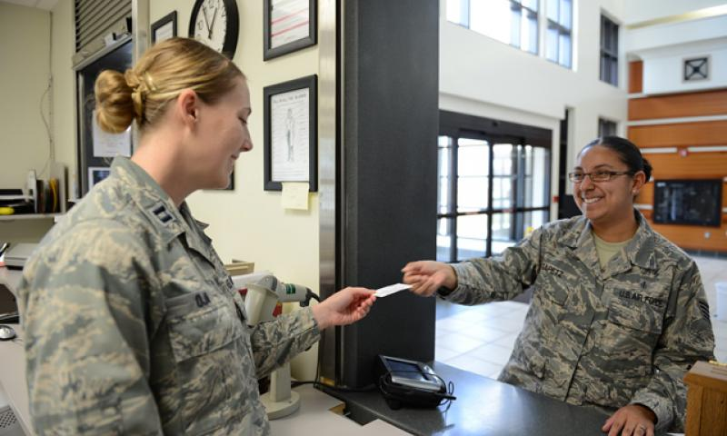 Capt. Kathryn Oja, 36th Medical Group pharmacist, receives a Self-Initiated Care Kit card from Staff Sgt. Sarai Gapetz, a patient at 36th MDG, Feb. 20, 2015, at Andersen Air Force Base, Guam. The pharmacy has processed more than 80 prescriptions since the beginning of this month for S.I.C.K. patients. (U.S Air Force photo by Airman 1st Class Arielle Vasquez/Released)