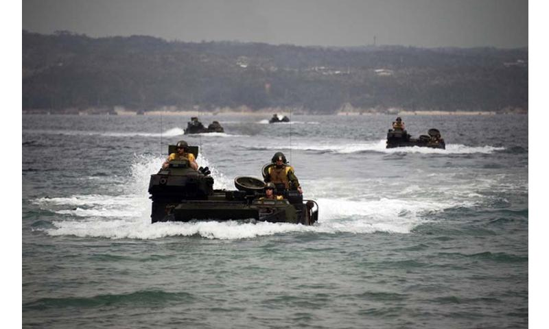 Marines with the III Marine Expeditionary Force maneuver amphibious assault vehicles through the water in formation March 5, 2013, at Camp Schwab on Okinawa, where the Futenma air station is slated to be moved. (Mark W. Stroud/Courtesy U.S. Marine Corps)