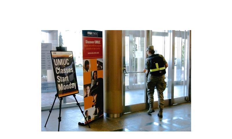 An airman walks past signs in an on-base shopping arcade advertising university classes due to start at Yokota Air Base, Japan, Monday. (Eric Guzman/Stars and Stripes)