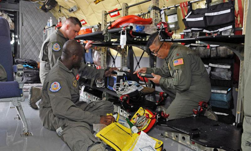 Senior Airman Kayode Idris and Maj. Joel  Villavert (front), and Senior Airman Zack Tarson with the 375th Aeromedical Evacuation Squadron prepare medical equipment before conducting an aeromedical evacuation mission on a KC-135R Stratotanker on Feb. 19. (Staff Sgt. Annie Edwards)