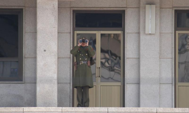 A North Korean soldier surveys the scene on the South Korea side of the Military Demarcation Line on March 13, 2013, at the Joint Security Area of the Demilitarized Zone. (Photo by Jon Rabiroff/Stars and Stripes)