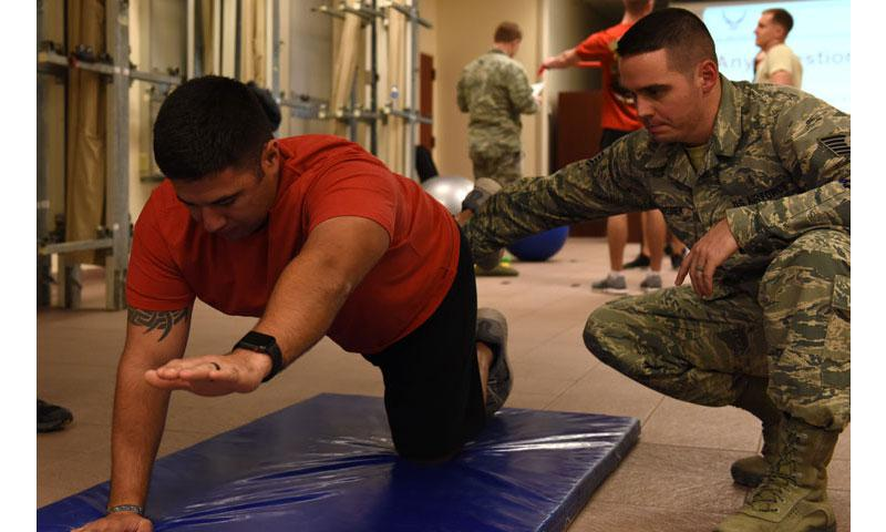 Tech. Sgt. Jacob Wielgosiek, 39th Medical Operations Squadron surgical services flight chief, assists Master Sgt. Matthew Wilt, 39th Civil Engineer Squadron additional duty first sergeant, with yoga poses during a physical therapy session at Incirlik Air Base, Turkey, Feb. 2, 2018. Yoga can increase balance and core strength, and help prevent potential injuries. (U.S. Air Force photo by Airman 1st Class Octavius Thompson)