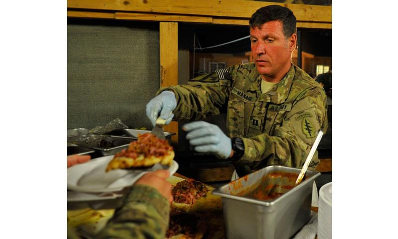 Capt. Rinaldo Manago, Base Defense Operations Center commander, hands a freshly made pizza to a Soldier at Bagram Air Field, Afghanistan, May 29, 2011. Army scientists at Natick Soldier Systems Center recently developed a pizza MRE that will go to full-scale production March 2018. (Photo Credit: U.S. Army photo by Sgt. Lizette Hart)