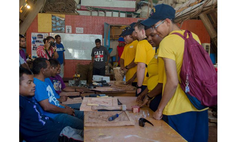 MAJURO, Republic of the Marshall Islands (March 16, 2017) Sailors assigned to the submarine tender USS Frank Cable (AS 40) observe the wood creations done by some of the men employed by Waan Aelon in Maiel, during a community relations project, March 16.  WAM is a program committed to empowering men and women in the Republic of the Marshall Islands and teaching them life skills. (U.S. Navy photo by Mass Communication Specialist 2nd Class Allen Michael McNair/Released)