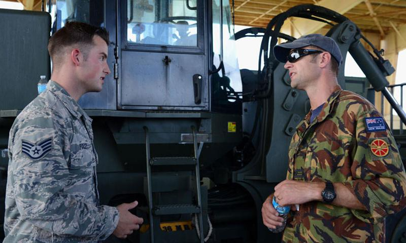 U.S. Air Force Staff Sgt. Joshua Foley, 36th Mobility Response Squadron aerial port supervisor, and Royal New Zealand Air Force Squadron Leader Brandon Purdue, operations squadron representative, discuss operational capabilities during Pacific Agility 16-1 March 15 , 2016, at Andersen Air Force Base, Guam.  (U.S. Air Force photo by Airman 1st Class Arielle Vasquez/Released)