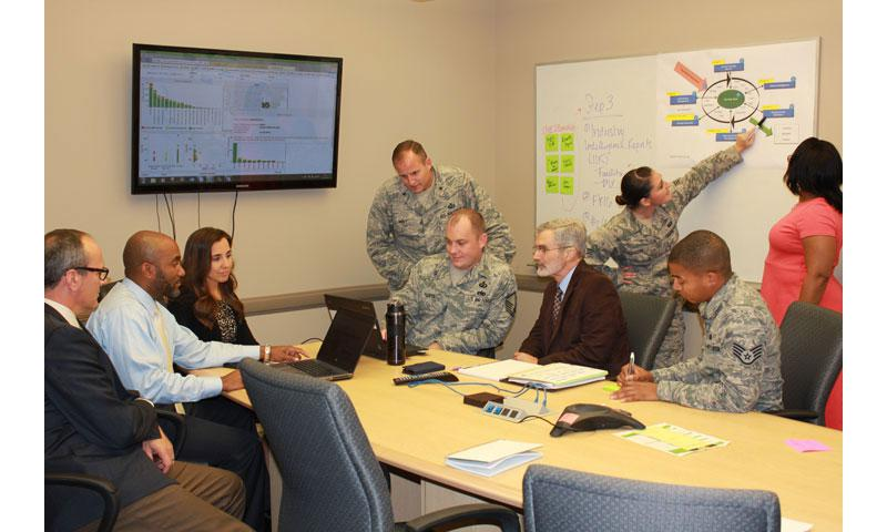 Brig. Gen. Cameron Holt, AFICA commander, and several members of his team discuss contracting strategies. Using a cost savings tracker, AFICA recently captured more than $1 billion in budgetary savings and cost avoidance. (Courtesy photo)