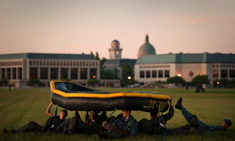 Midshipmen from the U.S. Naval Academy Class of 2016 conduct early morning physical training with an inflatable raft on the shore of the Severn River as part of the U.S. Naval Academy Sea Trials. (Todd Frantom/U.S. Navy)