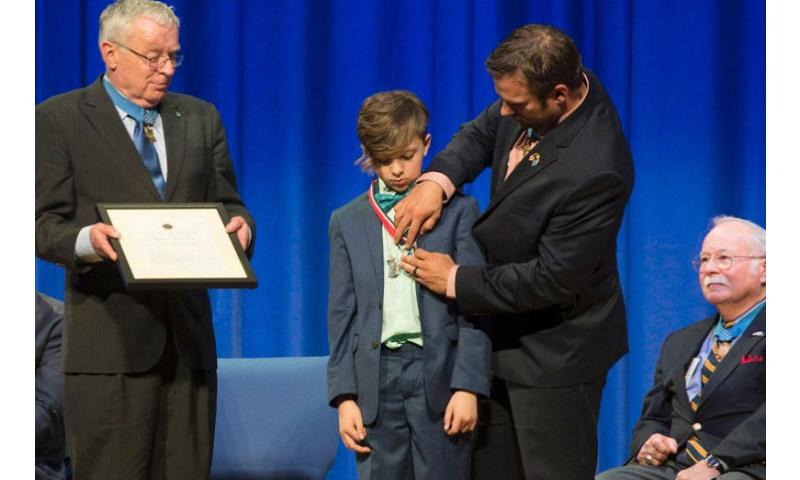 """Medal of Honor recipient Edward Byers presents Myles Eckert with the Young Hero Award during a ceremony Friday at Joint Base Myer-Henderson, Va. Other Medal of Honor recipients on hand included Thomas Kelley, left, and Harvey """"Barney"""" Barnum. (Meredith Tibbetts/Stars and Stripes)"""