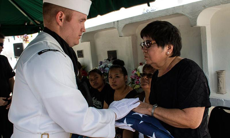 SANTA RITA, Guam – Master at Arms 1st Class Robert Schmidt presents the flag to the mother of late Petty Officer 2nd Class William Sablan Cruz.  Three Sailors and one airmen from the Joint Region Marianas (JRM) funeral honors detail performed at a funeral for a Guam veteran, April 1 at the Guam Veterans Cemetery.  Sailors and airmen devote their spare time to provide honors to veterans and their families at funerals on island, performing an average of four per month. Released/Jeff Landis, Major, USMC (Ret)
