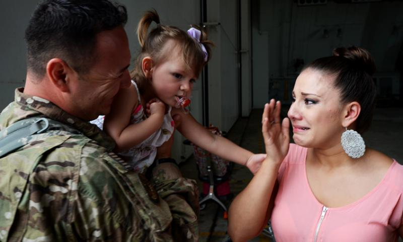 ANDERSEN AIR FORCE BASE, Guam — Staff Sgt. Jonathan Avila, 554th RED HORSE Squadron utilities technician, greets his wife and daughter during a homecoming in Hangar 1 on Andersen Air Force Base, Guam, April 16, 2013 The 554th RHS was deployed for seven months to Southwest Asia where they supported construction projects for eight different sites in and around the region. (U.S. Air Force photo by Senior Airman Benjamin Wiseman/Released)