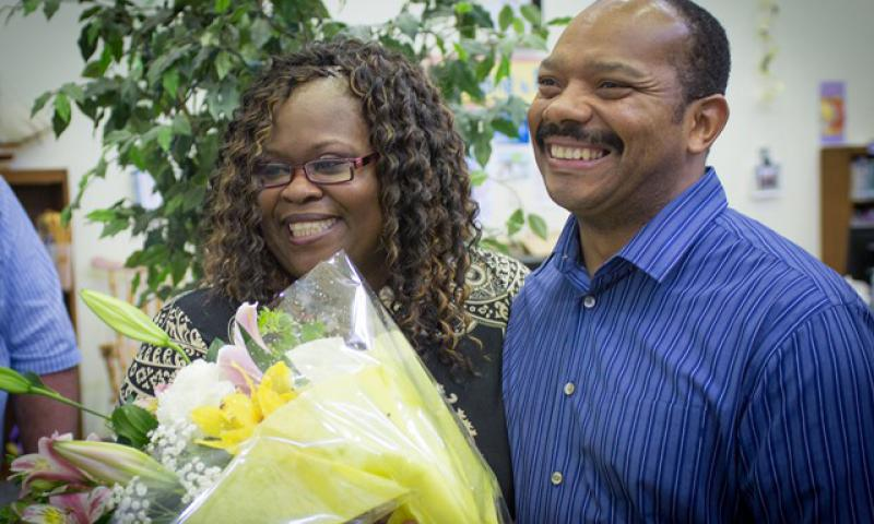 Ms. Michelle Moore-Robinson, DoDEA Pacific's Kinser Elementary School principal, receives flowers from her husband Michael in honor of her selection as the 2017 DoDEA Elementary School Principal of the Year.