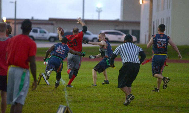 A 36th Security Forces Squadron member attempts to pull a flag from a 644th Combat Communications member as he tip-toes along the sideline during the flag football championship, April 20, 2015, at Andersen Air Force Base, Guam. The 36th SFS defeated the 644th CBCS 14-0 in the championship. (U.S. Air Force photo by Airman 1st Class Joshua Smoot/Released)