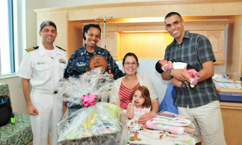 Capt. Jeff Plummer, U.S. Naval Hospital (USNH) Guam commanding officer, and USNH Guam Obstetrics and Gynecology Department Head Lt. Cmdr. Kelly Elmore present gifts to Capt. Andrew Howard, of 36th Maintenance Squadron, and his wife Elizabeth at the new hospital's Mother-Baby Unit April 22. The Howards' youngest daughter Bethany, born 1:37 p.m. April 20, was the first baby delivered at the new facility. (U.S. Navy photo by Jesse Leon Guerrero/Released)