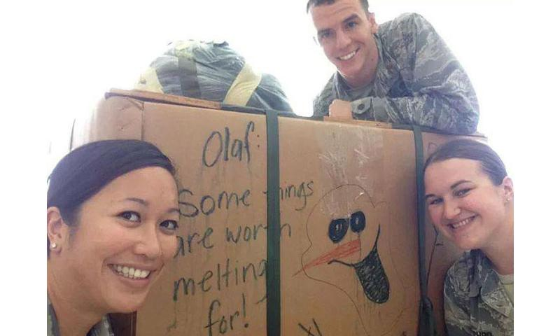 2nd Lt. Victoria Cachro (right), 36th Wing Plans, Programs and Readiness strategic planner, poses in front of a finished packaged box for Operation Christmas Drop in Hangar 3, Dec., 2014. Cachro volunteered more than 1,500 hours to the base and local community during the past year. (Courtesy photo)