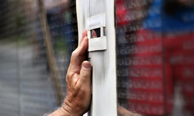Preparing to cut another name into the black granite of the Vietnam Veterans Memorial Wall, engraver Jim Lee carefully positions a stencil and a sandblasting platform at a designated spot on the Washington, D.C., memorial on Friday, May 2, 2014. (CARLOS BONGIOANNI/STARS AND STRIPES)