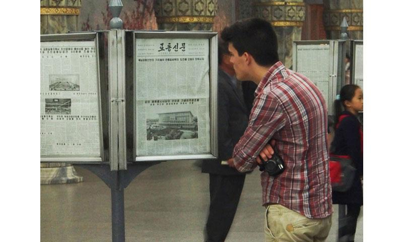 A tourist reads the state-run Rodong Sinmun newspaper at Yonggwang Metro Station in Pyongyang, North Korea. The U.S. State Department has issued a strongly worded and unusually detailed warning advising Americans not to visit North Korea, pointing to rising tensions on the divided peninsula and the detention of several foreigners in recent years. (Courtesy of Clay Gilliland/Wikicommons)