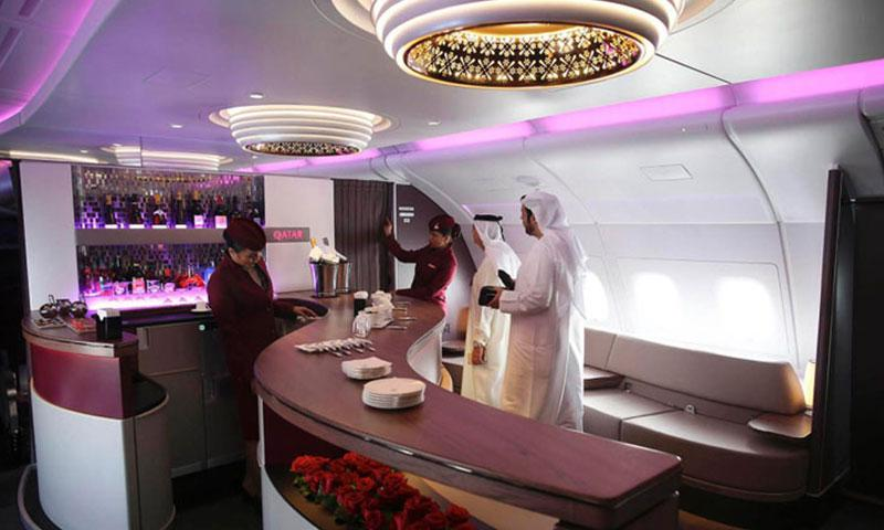 Flight crew members show visitors through the bar area for business class passengers aboard an Airbus A380-800 aircraft, operated by Qatar Airways Ltd., on the opening day of the 14th Dubai Air Show at Dubai World Central (DWC) in Dubai. Photo by Jasper Juinen, Bloomberg